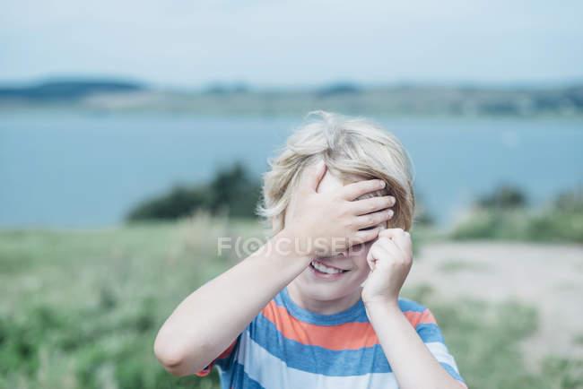 Menino de sorriso ao ar livre que cobre seus olhos — Fotografia de Stock