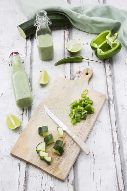 Скляна пляшка домашнього зеленого Gazpacho і інгредієнтів — стокове фото