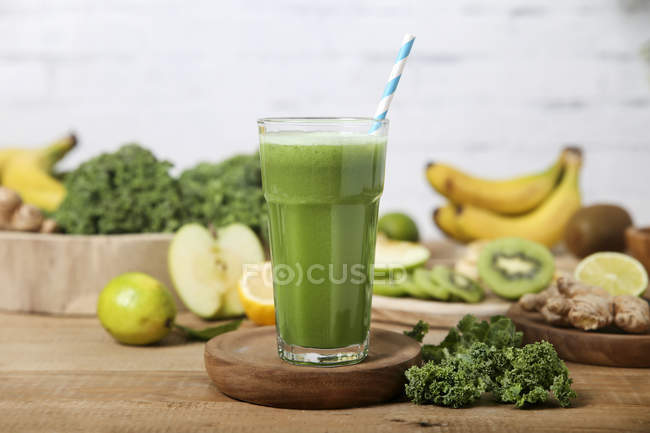 Green smoothie surrounded by ingredients — Stock Photo