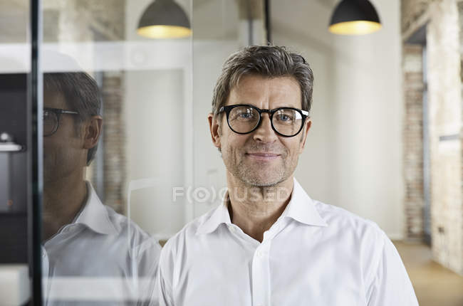 Portrait of smiling businessman wearing glasses — Stock Photo