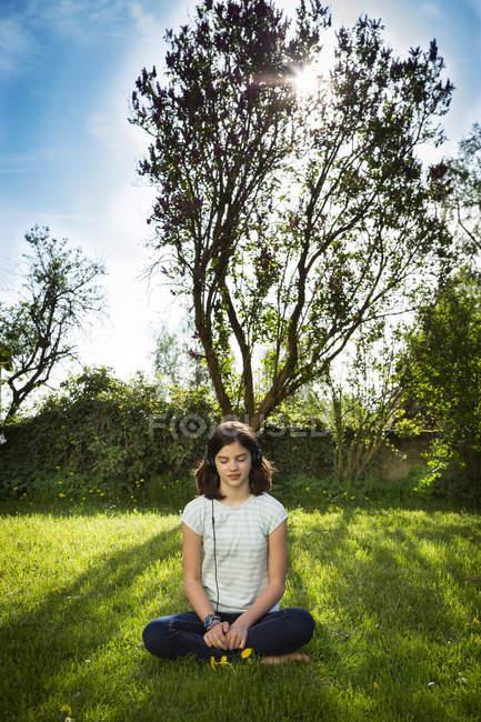 Дівчинка сидить на лузі і слухає музику навушниками. — стокове фото