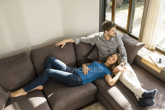 Couples affectueux détendant sur le sofa à la maison — Photo de stock
