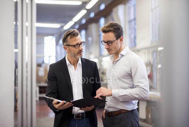 Deux hommes d'affaires dans l'usine regardant dossier — Photo de stock