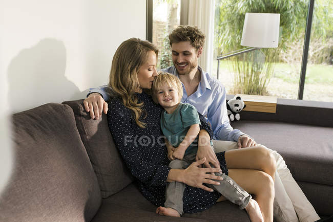 Happy parents sitting with son on sofa at home — Stock Photo