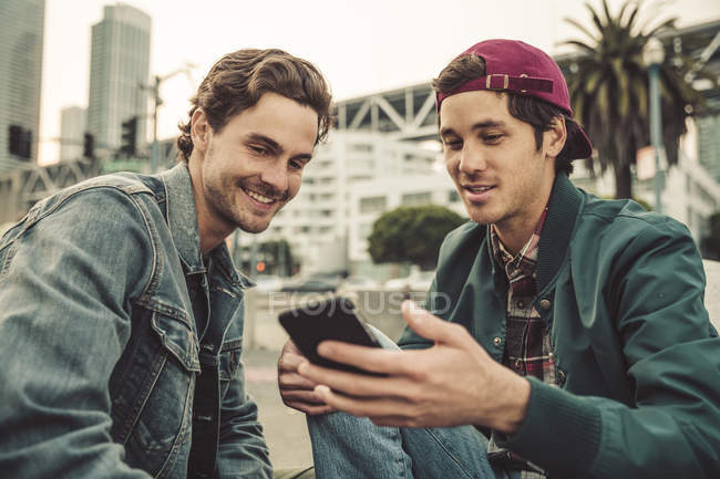 Two smiling young men sharing cell phone outdoors — Stock Photo