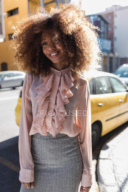 Verticale de belle jeune femme de sourire avec la coiffure afro dans la ville — Photo de stock