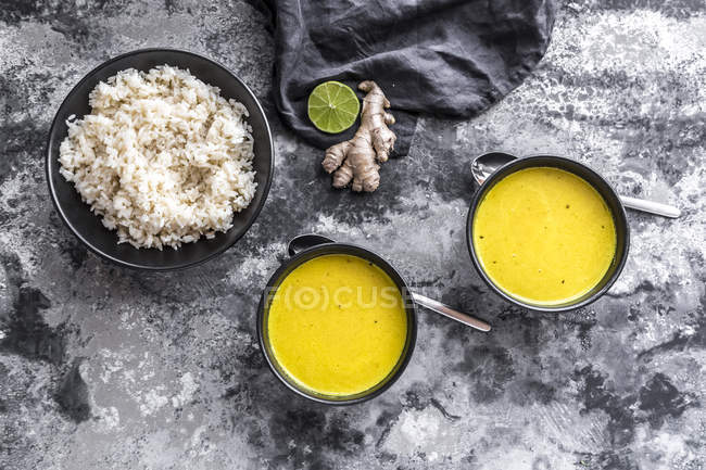 Curcuma-Kokossuppe, Reis, Schüssel, Ingwer und Limette — Stockfoto