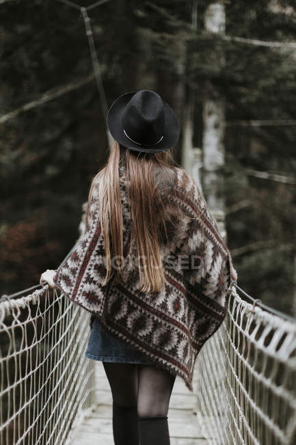 Back view of fashionable young woman wearing hat and poncho and walking on suspension bridge — Stock Photo