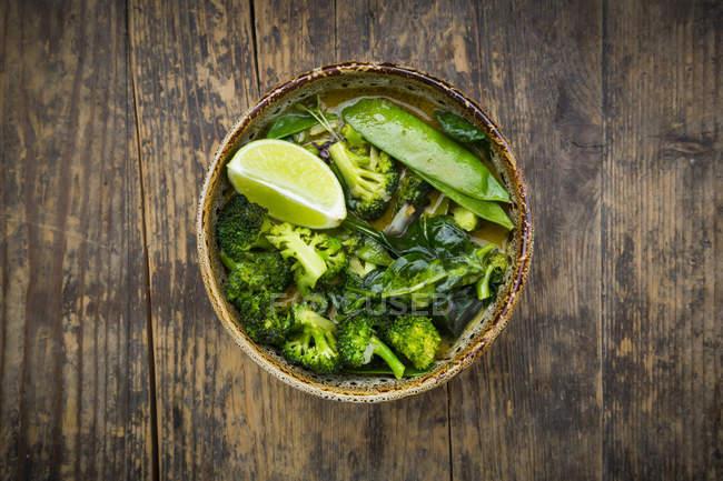 Schüssel mit grünem Thai-Curry mit Brokkoli, Pak Choi, Schneeerbsen, Babyspinat und Limette — Stockfoto