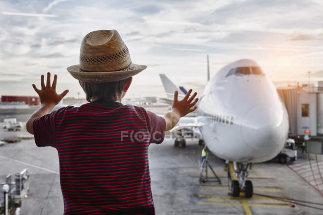 Niño con sombrero de paja mirando a través de la ventana al avión en el delantal - foto de stock
