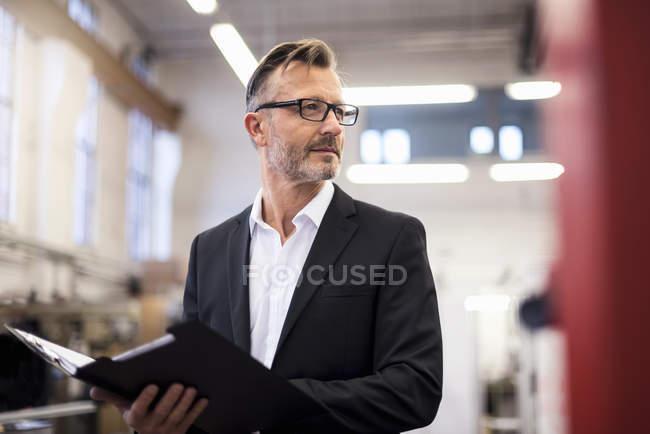 Mature businessman in factory holding folder — Photo de stock