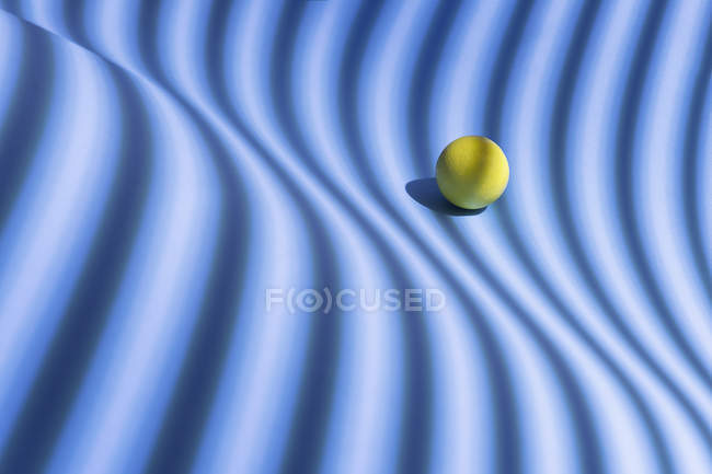 Yellow sphere over a geometric blue background, 3D Rendering — Stock Photo