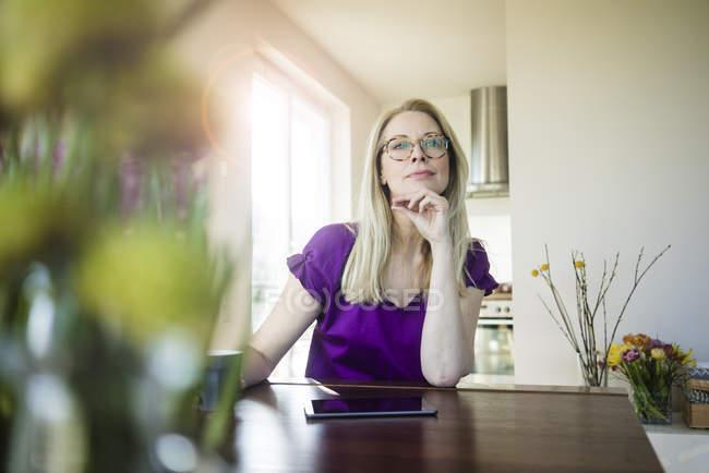 Портрет задумчивой женщины сидящей за столом дома — стоковое фото