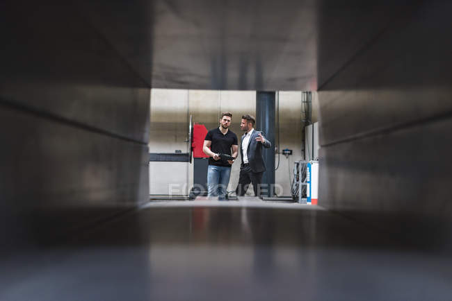 Due uomini con appunti che parlano in officina — Foto stock
