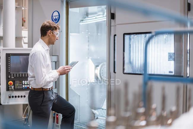 Empresário na máquina na fábrica vestindo óculos de segurança e segurando laptop — Fotografia de Stock