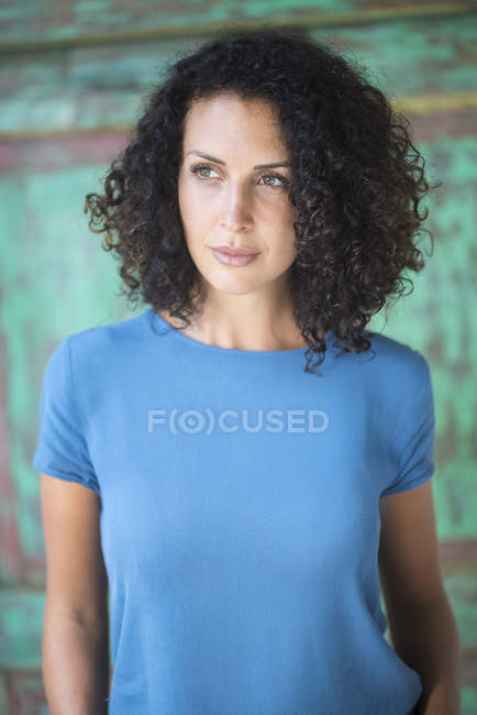 Portrait of woman with curly hair looking sideways — Stock Photo