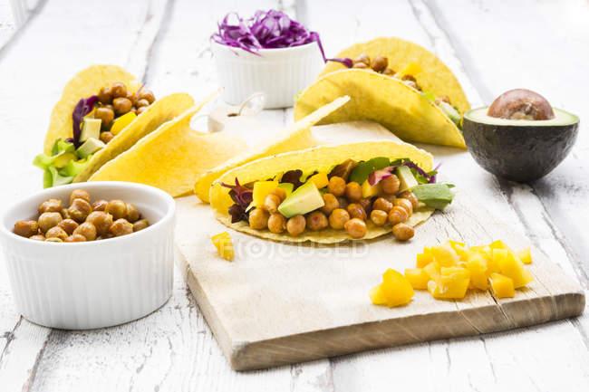 Вегетаріанські тако заповнені в куркумакуркуа Смажений курча гороху, жовта паприка, авокадо, салат і Червона капуста — стокове фото