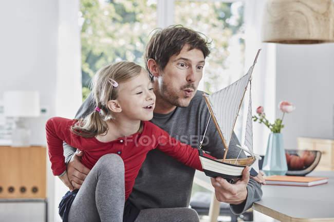 Щасливий батько і дочка грають з моделлю човен вдома — стокове фото