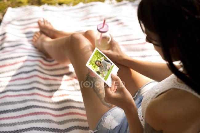 Молодая женщина, сидящая на одеяле, глядя на мгновенное фото — стоковое фото