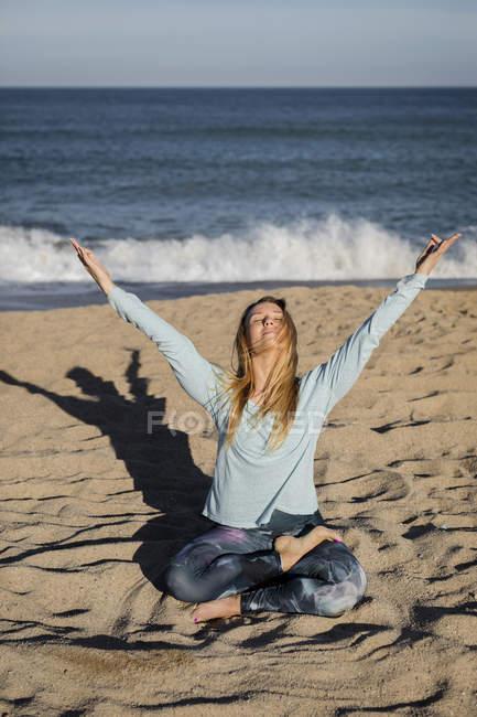 Женщина занимается йогой на пляже — стоковое фото