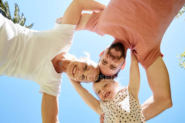Vista basso angolo di felice famiglia rannicchiarsi sotto il cielo blu — Foto stock