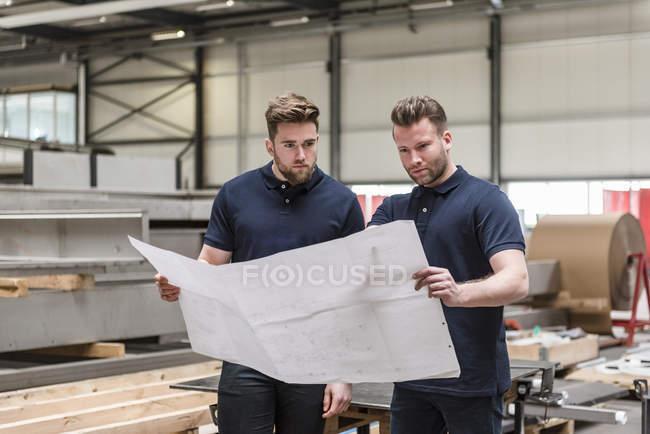 Двое мужчин рассматривают план на заводе — стоковое фото