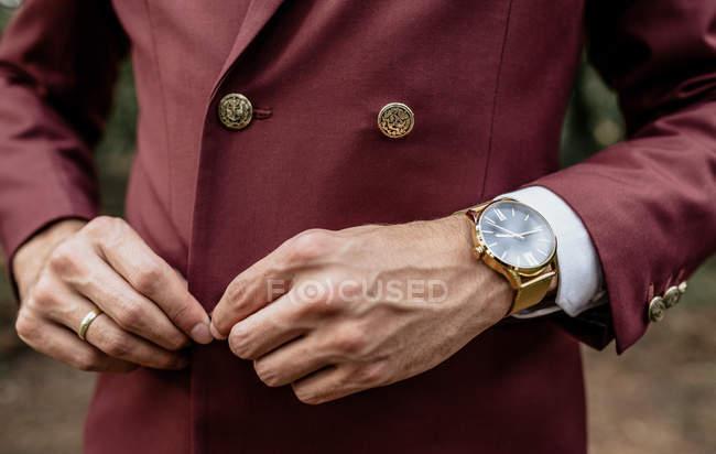 Nahaufnahme eines Mannes mit Anzug und goldener Uhr, der seine Jacke zuknöpft — Stockfoto