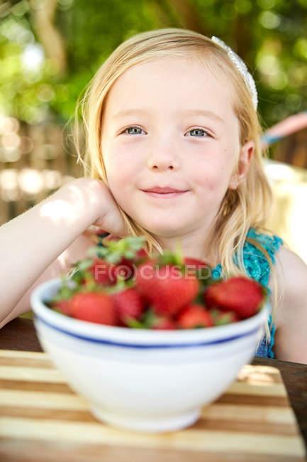 Портрет улыбающейся девушки с чашей клубники — стоковое фото