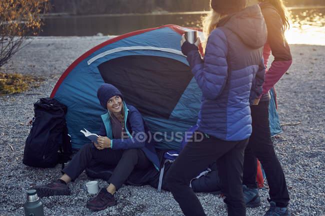 Groupe de randonneurs campant au bord du lac au coucher du soleil — Photo de stock