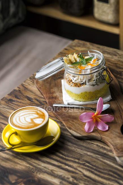 Muesli exótico con flor y taza de café sobre una mesa de madera - foto de stock