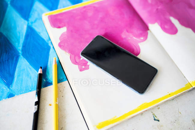 Smartphone lying on a notebook with a pink drawing in artist's studio — Stockfoto
