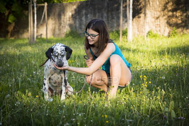 Girl feeding Dalmatian in the garden — Stock Photo