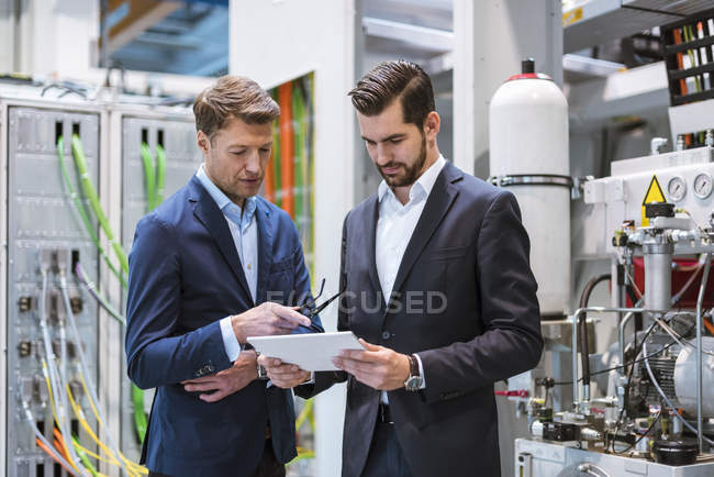 Two businessmen in factory looking at tablet — Photo de stock