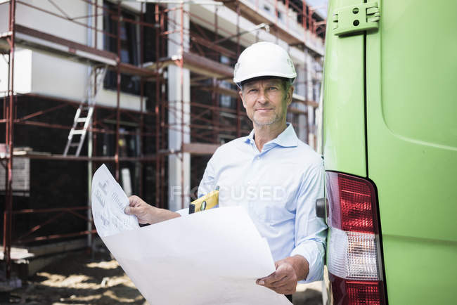 Portrait of architect with blueprint wearing hard hat on construction site — Stock Photo