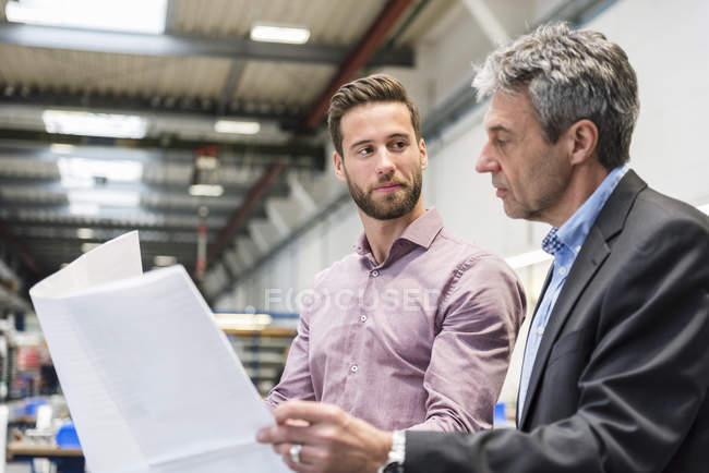 Businessmen with plan during meeting in production hall — Photo de stock