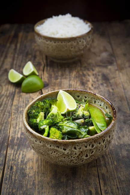 Grünes Thai-Curry mit Brokkoli, Pak Choi, Schneeerbsen, Babyspinat, Limette und Reisschale im Hintergrund — Stockfoto
