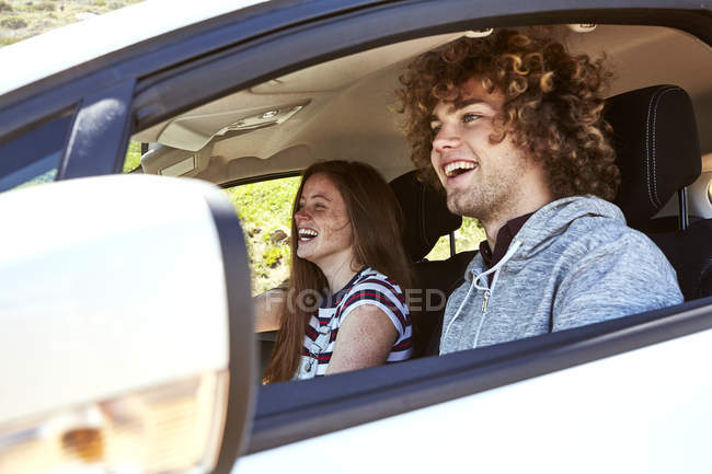 Laughing young woman with boyfriend driving car — Stock Photo