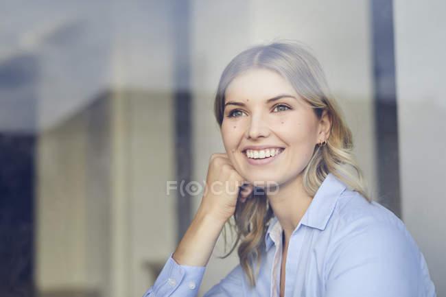 Retrato de la mujer de negocios de contenido mirando por la ventana - foto de stock