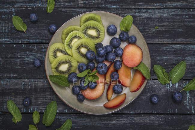 Тарелка с черникой и ломтиками киви и нектарина — стоковое фото