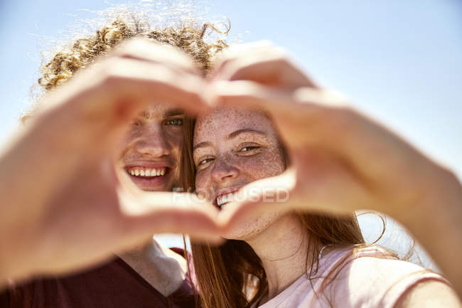 Happy young couple shaping heart with their hands — Stock Photo