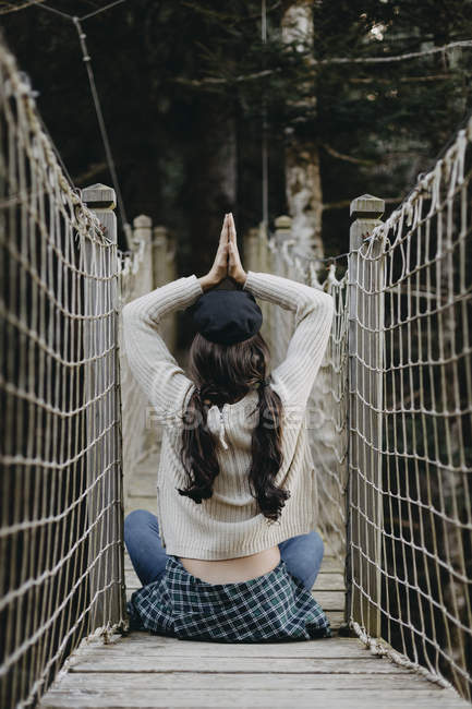 Young woman in yoga pose sitting on a suspension bridge — Stock Photo
