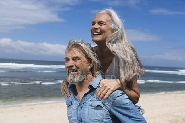 Handsome senior couple having fun at the beach — Stock Photo