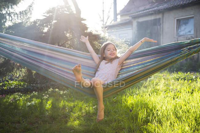 Ritratto di bambina felice seduta su un'amaca in giardino — Foto stock