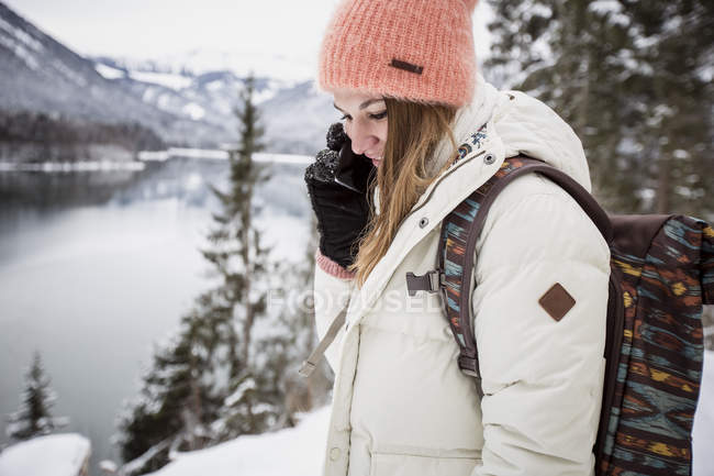 Mujer joven en el teléfono celular en el paisaje alpino de invierno con lago - foto de stock