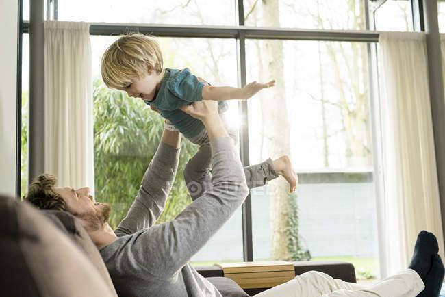 Pai feliz brincando com o filho no sofá em casa — Fotografia de Stock