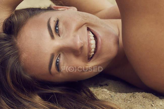 Портрет смеющейся молодой женщины, лежащей на пляже, крупным планом — стоковое фото