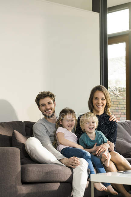Portrait of happy family sitting on sofa at home — Stock Photo