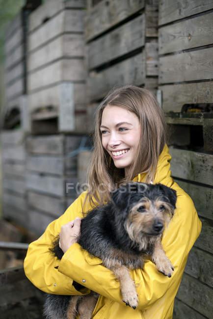 Усміхнена жінка на фермі стоїть на дерев'яних коробках і тримає собаку — стокове фото
