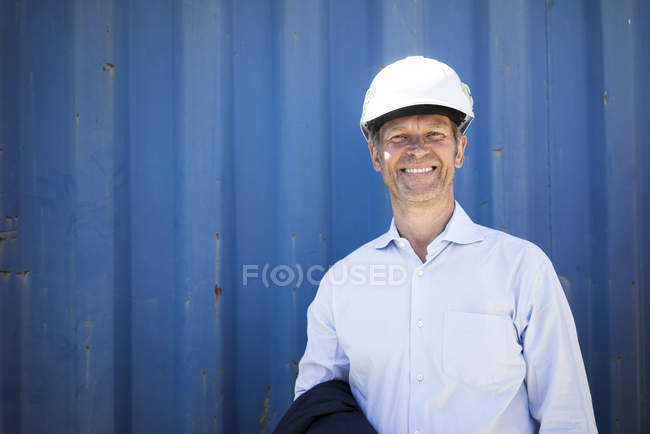 Portrait of smiling man wearing shirt and hard hat — Stock Photo