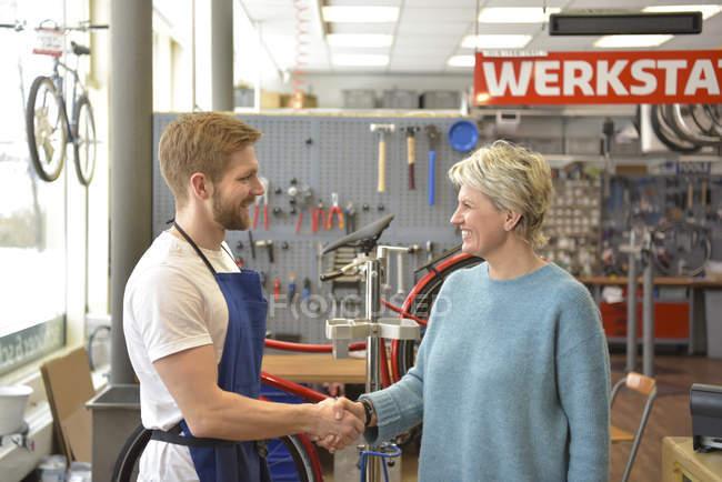 Venditore che aiuta il cliente nel negozio di biciclette — Foto stock